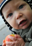 Baby boy with an apple. Baby boy outside wearing a cap and with a fresh apple in his hand Stock Image