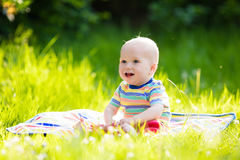 Baby boy with apple on family garden picnic Royalty Free Stock Photography