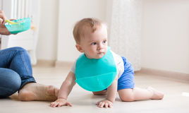 Baby boy in apron crawling on floor while mother trying to feed Royalty Free Stock Photos