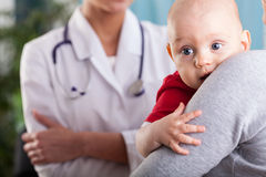 Baby boy in the arms of mother at doctor's office Royalty Free Stock Photos