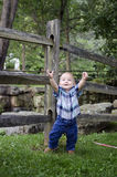Baby Boy with Arms Up. Young child posing by a wooden fence Royalty Free Stock Images