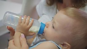 Baby boy, asleep with bottle. Pretty baby boy drinking milk from bottle, close up.