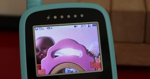 Baby boy in the babyphone monitor. Watching cute baby boy in the hd babyphone security monitor. Close up view portrait - DCi 4K resolution stock footage