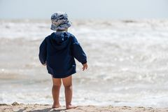 Baby boy barefoot at the beach from back stock images