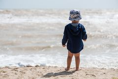Baby boy barefoot at the beach from back royalty free stock photo