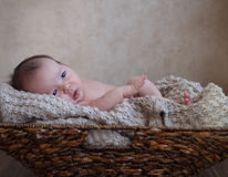 Baby boy in the basket on the wooden floor Royalty Free Stock Images