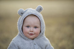 Baby boy in a bear suit at sunset Royalty Free Stock Images