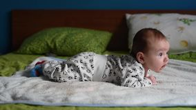 Baby boy in bed. Baby boy enjoying tummy time in bed stock footage