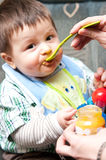 Baby boy being fed. Portrait of a baby boy being fed with spoon by his mother royalty free stock photos