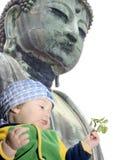 Baby boy below Great Buddah; Kamakura, Japan. Nine month old baby boy holding camelia twig below Great Buddah statue in Kamakura, Japan Stock Photography