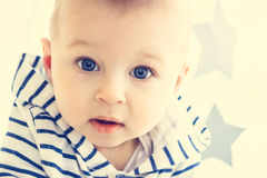 Baby boy with big blue eyes. A cute white baby boy with big blue eyes is looking surprisingly into the camera and wearing striped hooded sweater. Light Stock Image