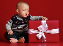 Baby boy with big blue eyes wearing warm sweater sitting in front of his present in wrapped box with ribbon over red background. royalty free stock images