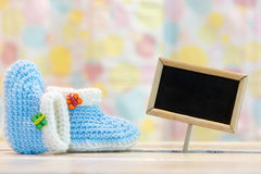 Baby boy birth card. Cute handmade light blue baby boy crochet booties and black chalkboard on pastel background - concept for baby boys birth and name Stock Photo