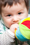 Baby boy bites toy. Closeup portrait of a baby boy biting his soft toy Stock Image