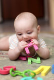 Baby boy biting letter Royalty Free Stock Photography