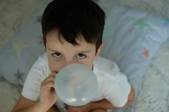 Baby boy is blowing the small air balloon stock images