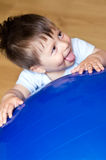 Baby boy and blue ball. Baby boy playing with a large blue, Pilates ball Royalty Free Stock Image
