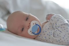 Baby boy with blue dummy lying royalty free stock images