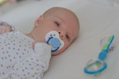 Baby boy with blue dummy lying royalty free stock photography
