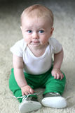 Baby boy with blue eyes. Cute baby boy with big blue eyes sitting upright on a white carpet Stock Photos