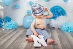 Baby boy with blue eyes barefoot in pants with suspenders, covered hidden under hat, sitting on wooden floor in studio Stock Image
