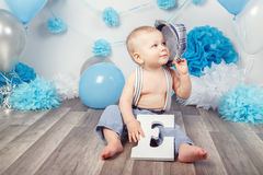 Baby boy with blue eyes barefoot  in pants with suspenders and hat, sitting on wooden floor in studio, holding large letter E Royalty Free Stock Photos