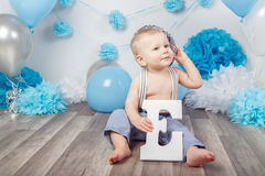 Baby boy with blue eyes barefoot  in pants with suspenders and hat, sitting on wooden floor in studio, holding large letter E, loo Stock Photography