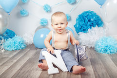 Baby boy with blue eyes barefoot in pants with suspenders and hat, sitting on wooden floor in studio, holding large letter N, loo Royalty Free Stock Image