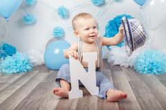 Baby boy with blue eyes barefoot in pants with suspenders and hat, sitting on wooden floor in studio, holding large letter N, loo Royalty Free Stock Photography