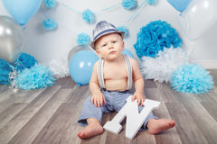 Baby boy with blue eyes barefoot in pants with suspenders and hat, sitting on wooden floor in studio, holding large letter N, loo Royalty Free Stock Photo