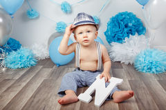 Baby boy with blue eyes barefoot in pants with suspenders and hat, sitting on wooden floor in studio, holding large letter N, loo Stock Photo