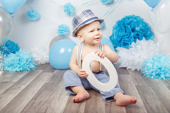 Baby boy with blue eyes barefoot  in pants with suspenders and hat, sitting on wooden floor in studio, holding large letter O, loo Royalty Free Stock Photography