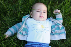 A baby boy in a blue jacket lying on the grass Royalty Free Stock Image