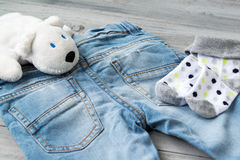 Baby boy blue jeans, socks and white toy bear on a wooden background royalty free stock image