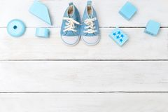 Baby boy blue shoes and wooden toys on a white wooden background Stock Images