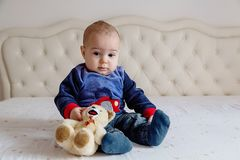 Baby boy in a blue sweater sitting on a white bed with a soft toy bear. Baby boy in a blue sweater and orange hair sitting on a white bed with a soft toy bear stock image
