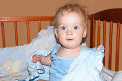 Baby boy. In blue towel smiles in bed Stock Photography