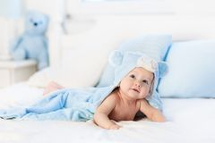 Baby boy in blue towel on white bed. Baby boy wearing diaper and blue towel in white sunny bedroom. Newborn child relaxing in bed after bath or shower. Nursery royalty free stock photos