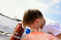 Baby boy on boat looking on water Royalty Free Stock Image