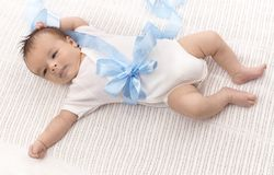 Baby boy in bodysuit and blue ribbon Royalty Free Stock Photography