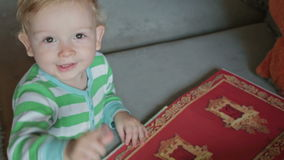 Baby boy with book point to camera stock footage