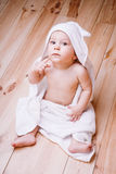 Baby boy with brown eyes is five months old wrapped in a white towel with ears on wooden background . Royalty Free Stock Photography