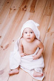 Baby boy with brown eyes is five months old wrapped in a white towel with ears on wooden background . Royalty Free Stock Photos