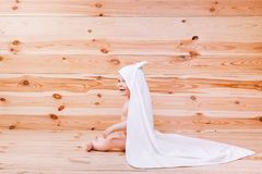 Baby boy with brown eyes is five months old wrapped in a white towel with ears on wooden background . Royalty Free Stock Images