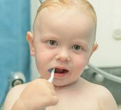 Baby boy brushing his teeth Stock Images