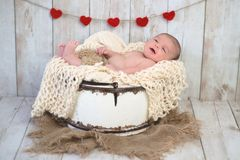 Baby Boy in a Bucket with Heart Garland Royalty Free Stock Image