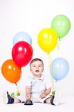 Baby boy with bunch of balloons Stock Image