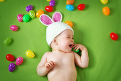 Baby boy in bunny hat lying on green blanket with easter eggs Royalty Free Stock Photography