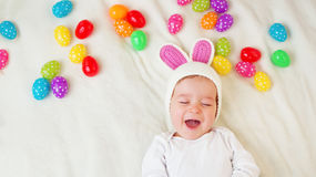 Baby boy in bunny hat lying on green blanket with easter eggs Stock Image