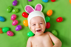 Baby boy in bunny hat lying on green blanket with royalty free stock photo
